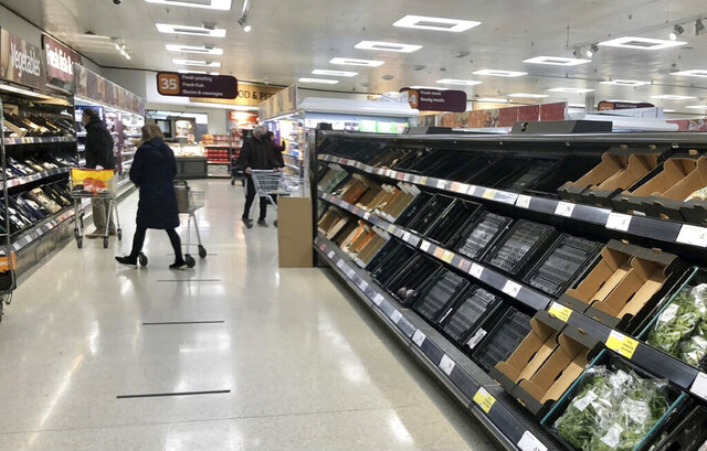 "Depleted shelves are seen in a Sainsbury's supermarker at the Forestside shopping centre in Belfast, Monday, Jan. 11, 2021. The U.K.'s biggest supermarket chains warned Wednesday, Jan. 13 that food supplies in Northern Ireland face disruption because of new checks imposed by Britain's departure from the European Union. After photos emerged showing empty shelves, the chief executives of Tesco, Sainsbury's, Asda, Iceland, Co-Op and Marks & Spencer wrote to the government saying there would be ""significant disruption"" unless urgent action was taken to fix an ""unworkable"" system. (David Young/PA via AP)"