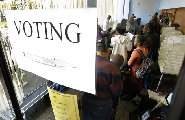 FILE- In a Nov. 3, 2008, file photo, voters wait to fill out absentee ballots the day before the general election in Detroit. People can cast absentee ballots in Michigan's March 10, 2020 presidential primary starting Saturday, Jan. 25, 2020.  (AP Photo/Paul Sancya, File)
