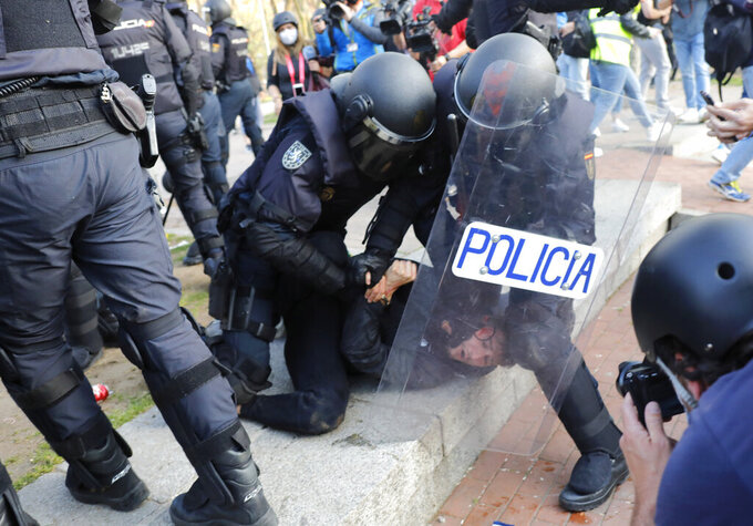 A protester is detained by Spanish police as they try to keep them away from supporters of the far-right Vox party during a party rally in Madrid's Vallecas neigborhood, a traditional left-wing bastion, Spain, Wednesday, April 7, 2021. Scuffles started when the national leader of Vox, Santiago Abascal, approached a crowd which had gathered to protest the party rally. Riot peace charged the bunches of protesters to keep them away from Abascal and other members of his party campaigning for upcoming regional elections in the area including Spain's capital. (AP Photo/Bernat Armangue)