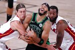Boston Celtics forward Jayson Tatum, center, struggles to maintain control of the ball as Miami Heat forward Kelly Olynyk, left, and Andre Iguodala, right, attempt to strip it away during the first half of an NBA conference final playoff basketball game, Thursday, Sept. 17, 2020, in Lake Buena Vista, Fla. (AP Photo/Mark J. Terrill)
