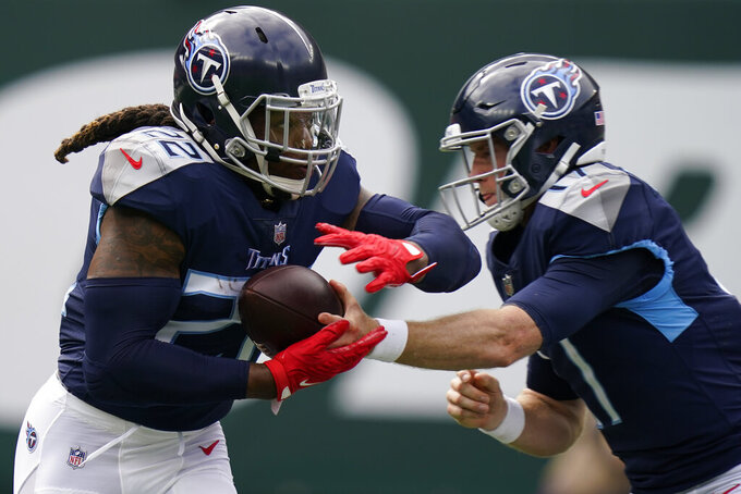 Tennessee Titans running back Derrick Henry (22) receives the ball from quarterback Ryan Tannehill, right, during the first half of an NFL football game against the New York Jets, Sunday, Oct. 3, 2021, in East Rutherford. (AP Photo/Seth Wenig)