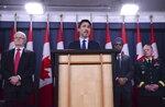 Prime Minister Justin Trudeau holds a press conference in Ottawa on Wednesday, Jan. 8, 2020, flanked by Transport Minister Marc Garneau (left), Defence Minister Harjit Sajjan and Gen. Jonathan Vance. (Sean Kilpatrick/The Canadian Press via AP)