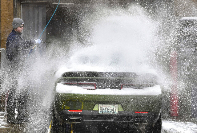 Marcus Smith, 23, sprays down a line of dirty cars with hot water at Mister Car Wash near downtown Spokane, Wash., Tuesday, Jan. 14, 2020. It didn't appear 20 degrees Fahrenheit (-6.7 C), ice and snow prevented him from cleaning vehicles. (Dan Pelle/The Spokesman-Review via AP)