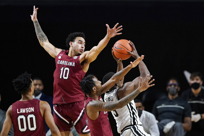South Carolina forward Justin Minaya (10) reaches for a rebound grabbed by Vanderbilt guard Maxwell Evans (3) in the second half of an NCAA college basketball game Saturday, Jan. 30, 2021, in Nashville, Tenn. (AP Photo/Mark Humphrey)