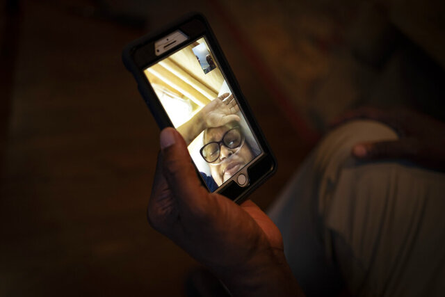 Mike Bishop video chats in Byram, Miss., with his wife, Bonnie Bishop, who is hospitalized 40 miles away, on Thursday, Oct. 8, 2020. He's hoping she'll be back by Thanksgiving. (AP Photo/Wong Maye-E)