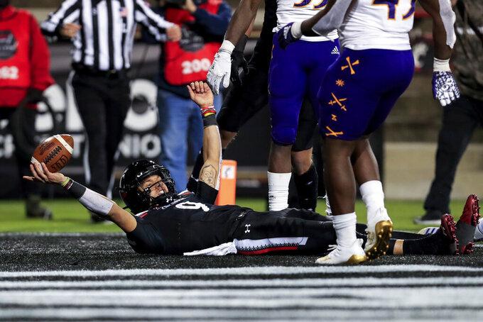 Cincinnati quarterback Desmond Ridder celebrates his touchdown during the first half of the team's NCAA college football game against East Carolina, Friday, Nov. 13, 2020, in Cincinnati. (AP Photo/Aaron Doster)