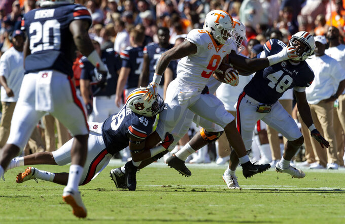 Auburn linebacker Darrell Williams (49) drags down Tennessee running back Tim Jordan (9) during the first half of an NCAA college football game, Saturday, Oct. 13, 2018, in Auburn, Ala. Auburn linebacker Montavious Atkinson (48) trails on the play. (AP Photo/Vasha Hunt)