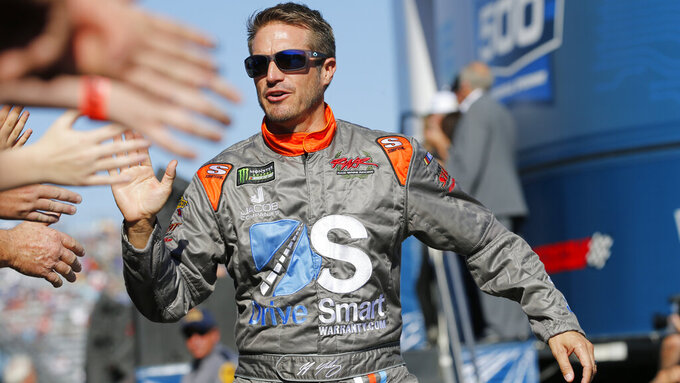 JJ Yeley greets fans during the NASCAR Cup Series race at Martinsville Speedway in Martinsville, Va., Sunday, Oct. 27, 2019. (AP Photo/Steve Helber)