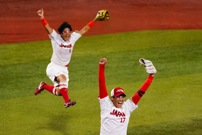 Japan's Yukiko Ueno (17) and Yu Yamamoto (5) celebrates after a softball game against the United States at the 2020 Summer Olympics, Tuesday, July 27, 2021, in Yokohama, Japan. Japan won 2-0. (AP Photo/Matt Slocum)