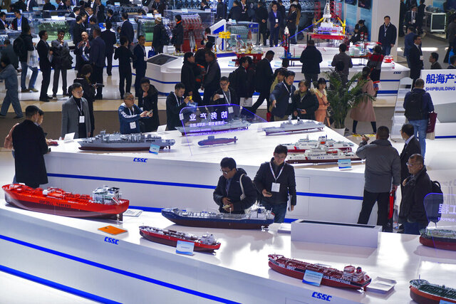 In this Tuesday, Dec. 3, 2019, photo, visitors look at the ship models exhibited by the China State Shipbuilding Corporation (CSSC) during the Marintec China exhibition in Shanghai, China. China's government promised Monday, Dec. 23, 2019, to open its oil, telecom and power markets wider to private competitors as the ruling Communist Party tries to shore up growth in the slowing, state-dominated economy. (Chinatopix via AP)