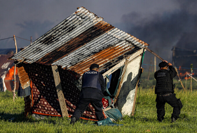 Police destroy a shack home as they carry out evictions at a squatters camp in Guernica, Buenos Aires province, Argentina, Thursday, Oct. 29, 2020. A court ordered the eviction of families who are squatting here since July, but the families say they have nowhere to go amid the COVID-19 pandemic. (AP Photo/Natacha Pisarenko)