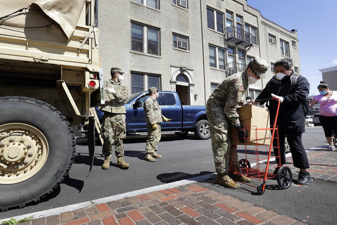 Massachusetts National Guard soldiers from the 181st Engineer Company, left, wear masks out of concern for the coronavirus as they distribute boxes of food, Tuesday, May 5, 2020, to people also wearing masks in Chelsea, Mass. (AP Photo/Steven Senne)