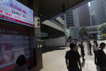 People walk past a bank's electronic board showing the Hong Kong share index at Hong Kong Stock Exchange Tuesday, Nov. 24, 2020. Asian shares were mostly higher Tuesday, encouraged by news on the development of coronavirus vaccines and more assurance for a transition of power in the U.S. to President-elect Joe Biden. (AP Photo/Vincent Yu)