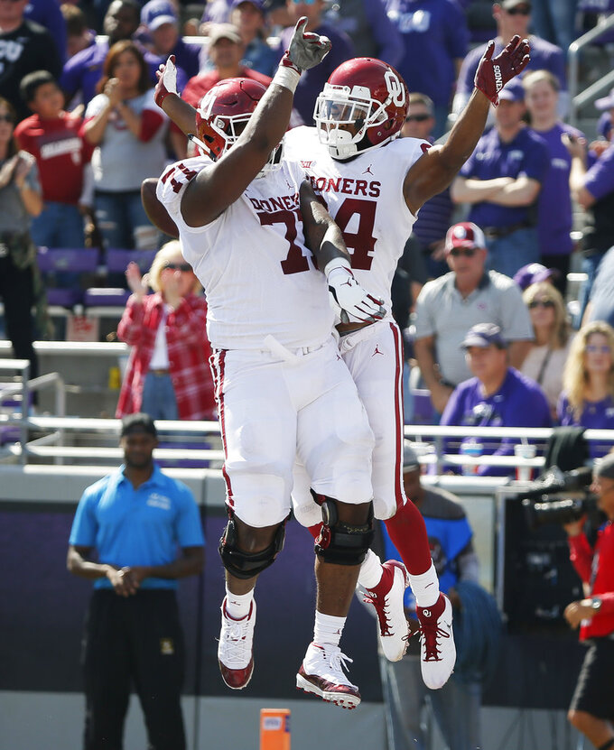 Oklahoma wide receiver Lee Morris (84) celebrates with offensive lineman Bobby Evans (71) after scoring a touchdown during the second half of an NCAA college football game against TCU, Saturday, Oct. 20, 2018, in Fort Worth, Texas. Oklahoma won 52-27. (AP Photo/Brandon Wade)