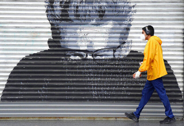 A pedestrian in a mask during the coronavirus outbreak walks by a mural of the late actor James Dean on Hollywood Boulevard, Saturday, April 4, 2020, in Hollywood section of Los Angeles. The new coronavirus causes mild or moderate symptoms for most people, but for some, especially older adults and people with existing health problems, it can cause more severe illness or death. (AP Photo/Mark J. Terrill)