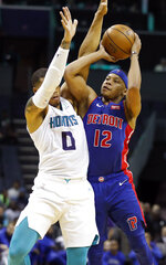 Charlotte Hornets' Miles Bridges (0) tries to block Detroit Pistons' Tim Frazier's shot during the second half of an NBA preseason basketball game in Charlotte, N.C., Wednesday, Oct. 16, 2019. The Pistons won 116-110. (AP Photo/Bob Leverone)