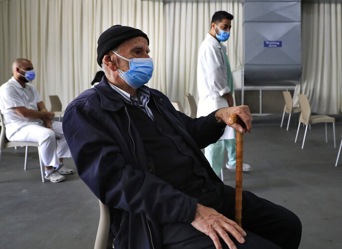 A man waits his turn to receive the Pfizer-BioNTech COVID-19 vaccine during a nationwide vaccination campaign, at the Saint George Hospital, in Beirut, Lebanon, Tuesday, Feb. 16, 2021. Lebanon launched its inoculation campaign after receiving the first batch of the vaccine — 28,500 doses from Brussels with more expected to arrive in the coming weeks. (AP Photo/Hussein Malla)