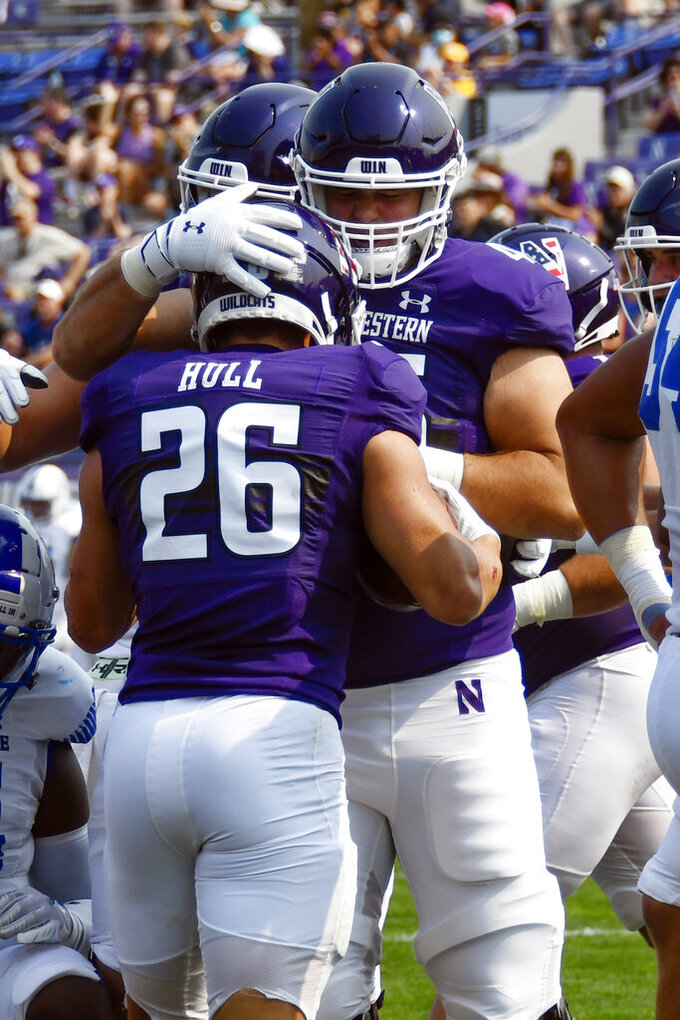 Northwestern running back Evan Hull (26) gets hugged by linebacker Cullen Coleman, right, after Hull scored a touchdown against Indiana State during the first half of an NCAA college football game in Evanston, Ill, Saturday, Sept. 11, 2021. (AP Photo/Matt Marton)