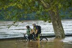 Amy Norwitz, back left, and Jason Lubken, front right,.walk their bikes through flood water on Kelly Drive at Midvale Ave. on Friday, July 12, 2019 in Philadelphia. A series of storms socked the Northeast with heavy rains and strong winds.  (Jessica Griffin/The Philadelphia Inquirer via AP)