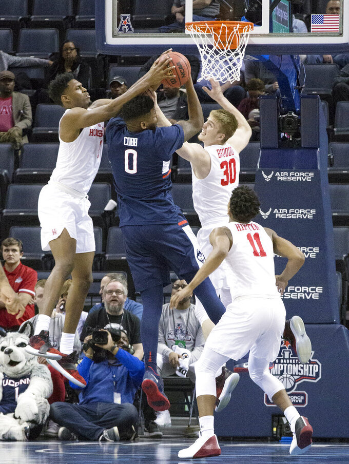 Houston players, from left, Chris Harris Jr., Caleb Broodo and Nate Hinton fight for a rebound against Connecticut's Eric Cobb in the second half of an NCAA college basketball game at the American Athletic Conference tournament Friday, March 15, 2019, in Memphis, Tenn. (AP Photo/Troy Glasgow)