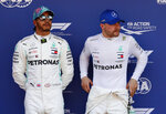 Mercedes driver Valtteri Bottas of Finland, right, pole position, is flanked buy his teammate Lewis Hamilton of Britain, second fastest time, after the qualifying session at the Barcelona Catalunya racetrack in Montmelo, just outside Barcelona, Spain, Saturday, May 11, 2019. The Formula One race will take place on Sunday. (AP Photo/Manu Fernandez)