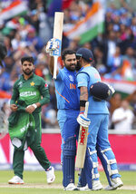 India's Rohit Sharma, center, celebrates with captain Virat Kohli, right, after scoring a century during the Cricket World Cup match between India and Pakistan at Old Trafford in Manchester, England, Sunday, June 16, 2019. (AP Photo/Aijaz Rahi)