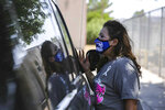 This Sept. 16, 2021, photo shows Yolanda Tafoya, a community school coordinator, giving out food and information flyers during Arrey Community Elementary School's weekly food pantry distribution event in Arrey, N.M. (Nathan J Fish/Las Cruces Sun-News via AP)