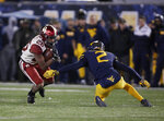 Oklahoma running back Kennedy Brooks (26) tries to get away from West Virginia safety Kenny Robinson Jr. (2) during the second half of an NCAA college football game Friday, Nov. 24, 2018, in Morgantown, W.Va. (AP Photo/Raymond Thompson)