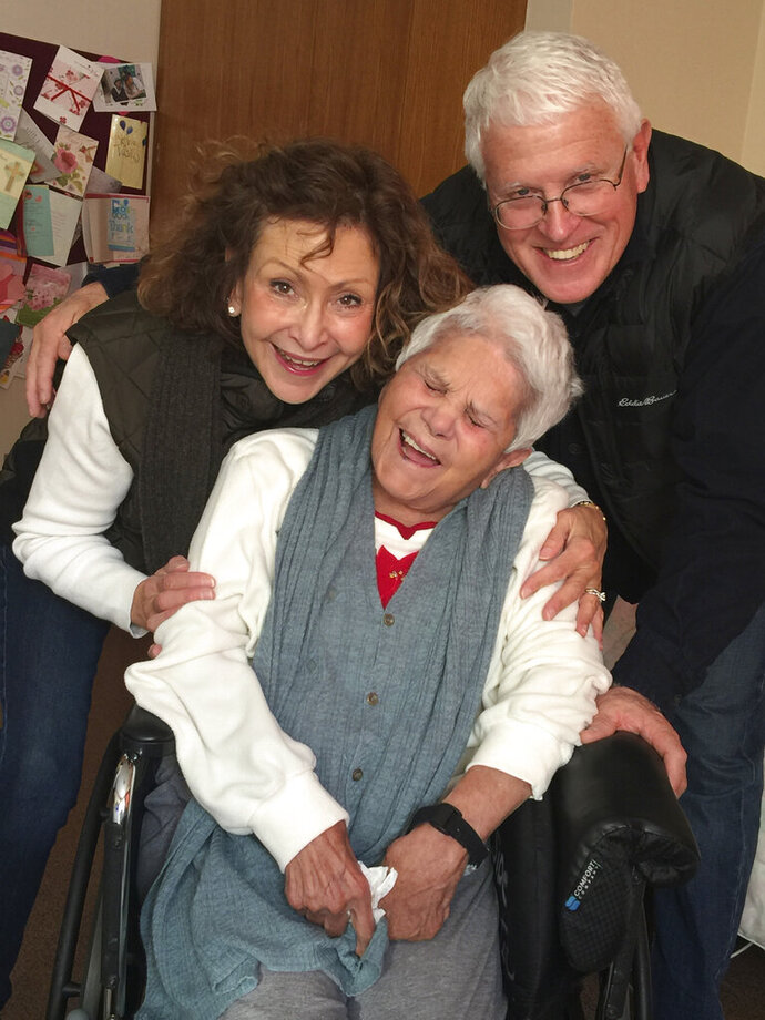 This Dec. 2017 photo provided by Julie Griffith shows Julie Griffith, left, with her mother Mabel Porter, center, and Griffith's husband, David, as they pose for a photo at a nursing home in Oregon, Ohio. The Griffiths are among those advocating to allow cameras inside long-term care facilities. Visitation bans at nursing homes because of the coronavirus have sparked renewed interest in legislation to allow the cameras.(Julie Griffith/Julie Griffith via AP)