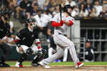 Boston Red Sox's Travis Shaw, right, watches his three-run home run in the third inning as Chicago White Sox catcher Yasmani Grandal, center, and umpire Dan Bellino, left, look on during a baseball game, Saturday, Sept. 11, 2021, in Chicago. (AP Photo/Jeff Haynes)
