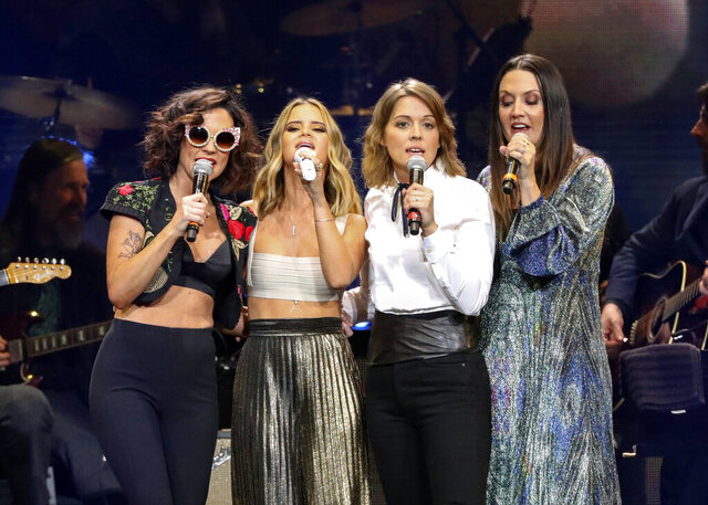 FILE - Amanda Shires, from left, Maren Morris, Brandi Carlile, and Natalie Hemby of The Highwomen perform at Loretta Lynn's 87th Birthday Tribute at Bridgestone Arena on Monday, April 1, 2019, in Nashville, Tenn. The Highwomen won three awards, including album, song and duo/group of the year, at the Americana Honors and Awards and the late John Prine was given artist of the year. The Americana Music Association announced the winners online this year after their awards show, normally held in Nashville, Tennessee, was cancelled because of the pandemic. (Photo by Al Wagner/Invision/AP, File)