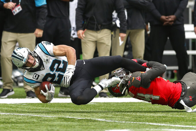 Carolina Panthers running back Christian McCaffrey (22) is tackled by Tampa Bay Buccaneers strong safety Darian Stewart (24) during the first quarter of an NFL football game, Sunday, Oct. 13, 2019, at Tottenham Hotspur Stadium in London. (AP Photo/Alastair Grant)
