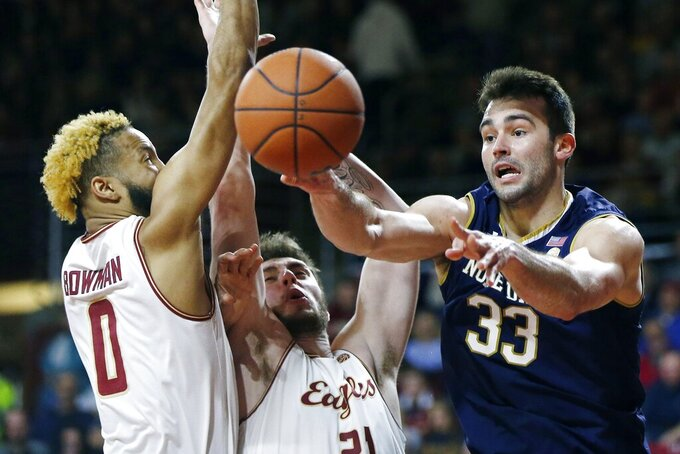 Notre Dame's John Mooney (33) passes off against Boston College's Ky Bowman (0) and Nik Popovic (21) during the second half of an NCAA college basketball game in Boston, Saturday, Feb. 2, 2019. (AP Photo/Michael Dwyer)