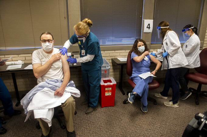 Pharmacist Darrell Childress and Registered Nurse Brooke Bailey prepare to receive COVID-19 vaccine at a clinic setup at the East Alabama Medical Center Education Center in Montgomery, Ala., on Wednesday, Dec. 16, 2020. (Jake Crandall/The Montgomery Advertiser via AP)