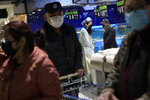 A masked woman wearing a raincoat and cover her head with a plastic bag shops for food with others at a supermarket in Wuhan in central China's Hubei province, Monday, Feb. 10, 2020. China reported a rise in new virus cases on Monday, possibly denting optimism that its disease control measures like isolating major cities might be working, while Japan reported dozens of new cases aboard a quarantined cruise ship. (Chinatopix via AP)