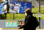 FILE - In this April 2, 2020, file photo, a pedestrian wears a hat and a face mask on Sunset Blvd., in the Echo Park neighborhood of Los Angeles. With no games being played, recent sports headlines have centered around hopes and dreams — namely, the uncharted path leagues and teams must navigate to return to competition in the wake of the pandemic. (AP Photo/Damian Dovarganes, File)