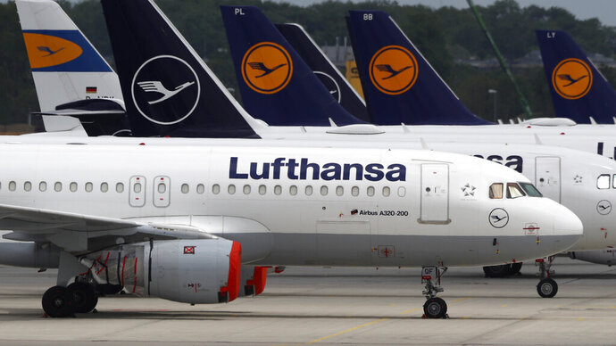 Aircrafts of the German airline Lufthansa are parked at the airport in Munich, Germany, Tuesday, May 26, 2020. Germany on Monday approved a 9 billion-euro ($9.8 billion) aid package for stricken airline Lufthansa to keep a major employer going through the turbulence of the coronavirus pandemic. (AP Photo/Matthias Schrader)