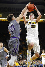 Iowa guard Joe Wieskamp (10) shoots over Northwestern forward A.J. Turner (21) during the second half of an NCAA college basketball game, Sunday, Feb. 10, 2019, in Iowa City, Iowa. Iowa won 80-79. (AP Photo/Charlie Neibergall)