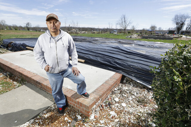 In this March 26, 2020, photo, Jose Cojom stands on the front step of what remains of his home after it was destroyed by a tornado in Cookeville, Tenn. Like thousands of other Middle Tennesseans, Cojom's life has been upended by back-to-back disasters. Residents still reeling from the deadly twisters of March 3 now have to confront life in the age of coronavirus. (AP Photo/Mark Humphrey)