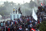 Protesters take control of some concrete walls and barriers erected by security forces to close the Sinak bridge leading to the Green Zone government areas, during clashes between Iraqi security forces and anti-government demonstrators in Baghdad, Iraq, Saturday, Nov. 16, 2019. Security and medical sources say protesters advanced deeper toward the fortified seat of Iraq's government, after security forces pulled back following a night of violent altercations. (AP Photo/Hadi Mizban)