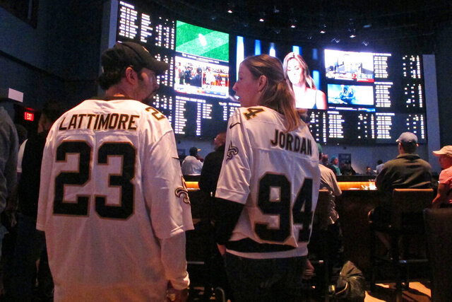Football fans wait for kickoff in the sports betting lounge at the Ocean Casino Resort on Sept. 9, 2018,  in Atlantic City, N.J. On Wednesday, Jan. 6, 2021, New York's governor did an about-face and embraced mobile sports betting as a way to deal with financial losses from the coronavirus pandemic, and a company that tracks gambling legislation and performance predicted revenue from legal sports betting could reach $3.1 billion in 2021 and as much as $10 billion within five years. (AP Photo/Wayne Parry)
