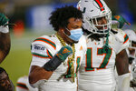 Miami linebackers Corey Flagg Jr. (11) and Waynmon Steed (17) celebrate on the sideline after forcing a turnover by Duke during the second half of an NCAA college football game Saturday, Dec. 5, 2020, in Durham, N.C. (Nell Redmond/Pool Photo via AP)