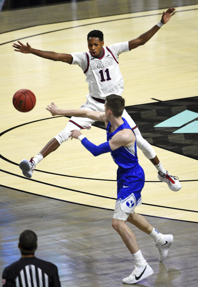 Gonzaga guard Joel Ayayi (11) defends against BYU guard Spencer Johnson during the second half of an NCAA college basketball game for the West Coast Conference men's tournament championship Tuesday, March 9, 2021, in Las Vegas. (AP Photo/David Becker)