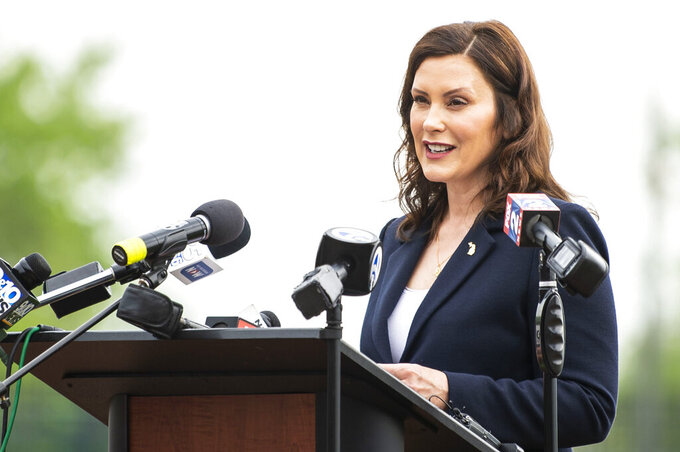 Michigan Gov. Gretchen Whitmer speaks during a press event providing an update on the state's COVID-19 response at Dow Diamond on Thursday, May 20, 2021, in Midland, Mich. Michigan will fully lift outdoor capacity limits on June 1 and, starting July 1, end indoor gathering caps that were put in place to curb COVID-19, Whitmer announced Thursday in a major loosening of economic restrictions.  (Kaytie Boomer/The Bay City Times via AP)