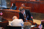 State Sen. Kirk Talbot, R-River Ridge, talks with Sen. Jay Morris, R-Monroes, as the Senate convenes in the Senate chamber in Baton Rouge, La., Monday, May 4, 2020. With some in masks and others uncovered, Louisiana lawmakers Monday resumed the final four weeks of a legislative session stalled by the coronavirus, trying to get their arms around the scale of the budget problems caused by the outbreak. The return to the Capitol has caused a new rift between Republicans, who hold the majority and pushed for a restart of work, and Democrats who said it was too risky to have hundreds of people in the building in a state that is one of the nation's hot spots for the COVID-19 disease caused by the virus.(AP Photo/Gerald Herbert)