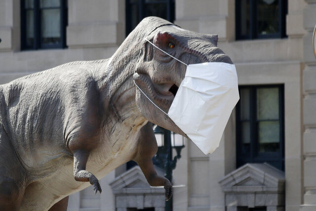 A dinosaur replica wears a mask outside Union Station in Kansas City, Mo., Wednesday, Aug. 5, 2020. The dinosaur is promoting a Dinosaur Road Trip exhibit. (AP Photo/Orlin Wagner)