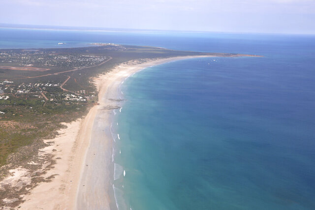 This aerial photo shows Cable Beach and the town of Broome, Western Australia, on June 24, 2014. A 55-year-old man died Sunday, Nov. 22, 2020 after being attacked by a shark off Cable Beach, a popular tourist spot on Australia's Indian Ocean coast, the eighth fatality in the country this year. (Kim Christian/AAP Image via AP)