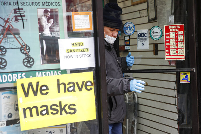 A customer leaves a shop advertising personal protective equipment near Elmhurst Hospital Center, Wednesday, March 25, 2020, in New York. Gov. Andrew Cuomo sounded his most dire warning yet about the coronavirus pandemic Tuesday, saying the infection rate in New York is accelerating and the state could be as close as two weeks away from a crisis that sees 40,000 people in intensive care. Such a surge would overwhelm hospitals, which now have just 3,000 intensive care unit beds statewide. (AP Photo/John Minchillo)