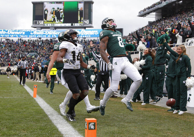 Michigan State's Jalen Nailor (8) celebrates after scoring a touchdown against Purdue's Antonio Blackmon (14) as Michigan State quarterback Rocky Lombardi, left rear, trails during the fourth quarter of an NCAA college football game, Saturday, Oct. 27, 2018, in East Lansing, Mich. Michigan State won 23-13. (AP Photo/Al Goldis)