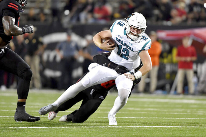 Coastal Carolina quarterback Bryce Carpenter (12) is tackled by an Arkansas State defender after a run during the first half of an NCAA college football game Thursday, Oct. 7, 2021, in Jonesboro, Ark. (AP Photo/Michael Woods)